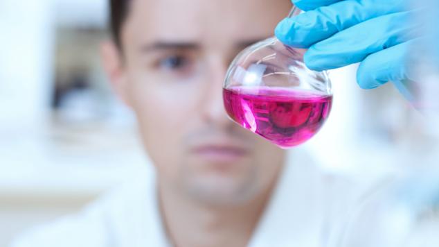 Scientist examines purple liquid in a beaker.